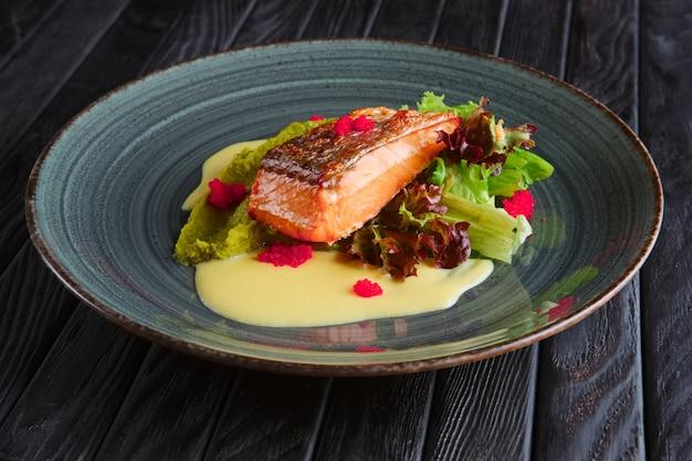 Filet de saumon frit avec feuilles de salade et sauce à la crème décorée de caviar