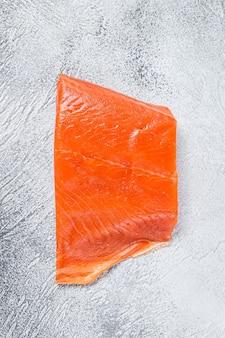 Filet de saumon fumé sur une table en bois sur blanc. vue de dessus.