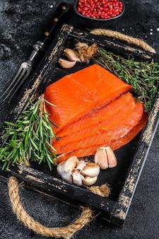 Filet de saumon fumé en tranches dans un plateau en bois aux herbes