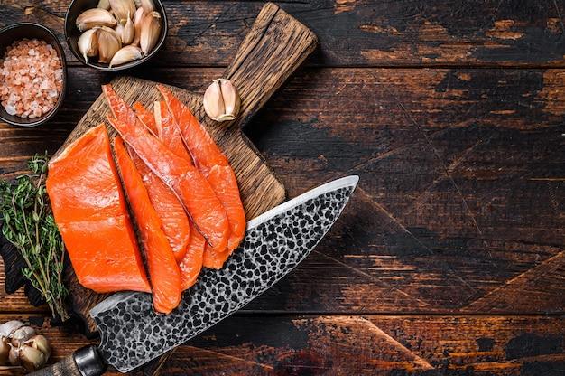 Filet de saumon fumé en tranches sur une planche à découper en bois avec des herbes