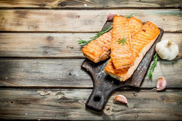 Filet de saumon grillé à l'ail et au romarin. sur un bois.