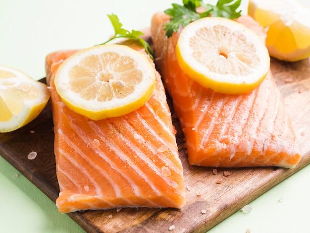 Filet de saumon sur une planche en bois avec des tranches de citron