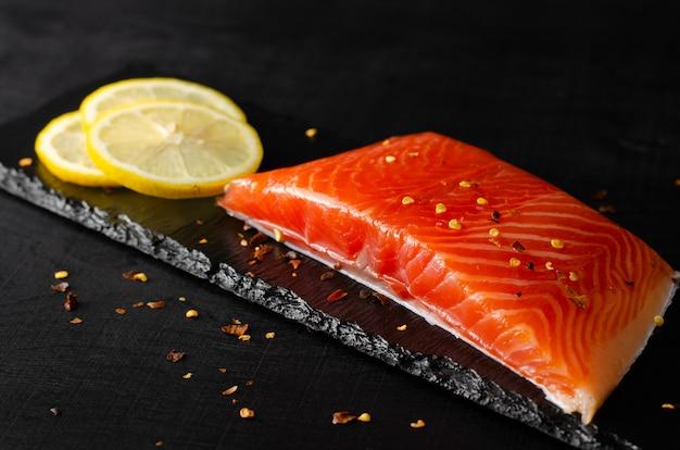 Filet de saumon et tranches de citron sur fond noir