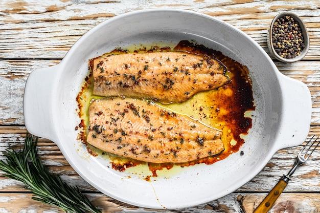 Filet de saumon ou de truite cuit au four. fond en bois blanc. vue de dessus.