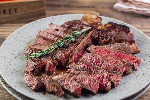Filet de steak barbecue de viande de porc de boeuf rouge grillé avec brin de romarin et sauce piquante servi sur plaque blanche.