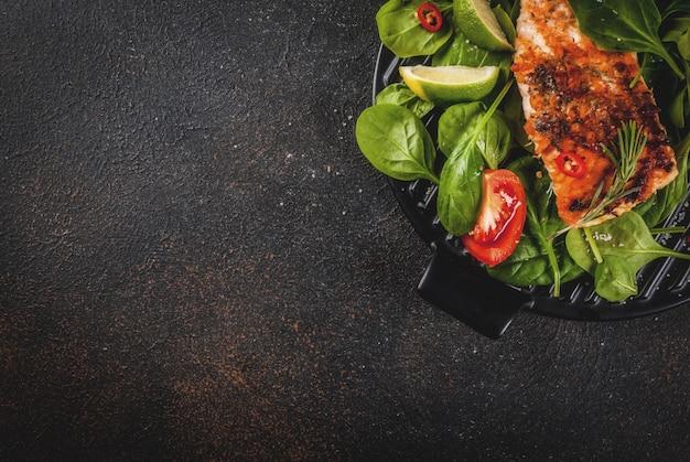 Filet de steak de saumon grillé avec légumes frais, épinards et citron vert, vue de dessus de table rouillé foncé