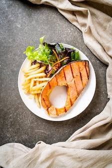 Filet de steak de saumon grillé avec légumes et frites sur plaque