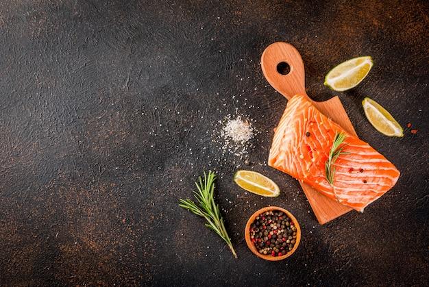 Filet de steak de saumon de poisson cru frais aux épices citron vert sel de romarin sur fond rouillé foncé