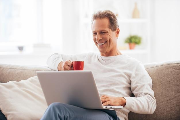 Filet de surf à la maison. homme d'âge mûr gai travaillant sur un ordinateur portable et buvant du café assis sur le canapé à la maison