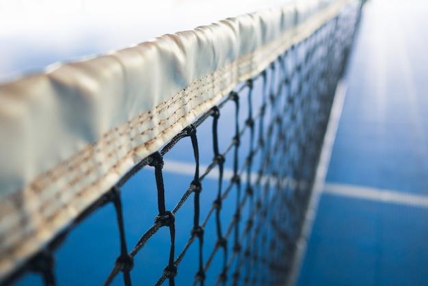 Filet de tennis avec une bande blanche dans une cour bleue floue