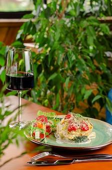 Filet de truite aux tomates cerises et fromage, servi avec légumes et vin rouge. concept de déjeuner méditerranéen