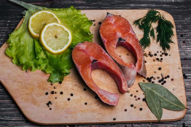 Filet de truite de poisson rouge frais coupé en tranches sur une planche de bois