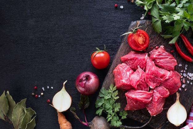 Filet de veau sur une planche à découper en bois avec tomates cerises, piment et herbes.