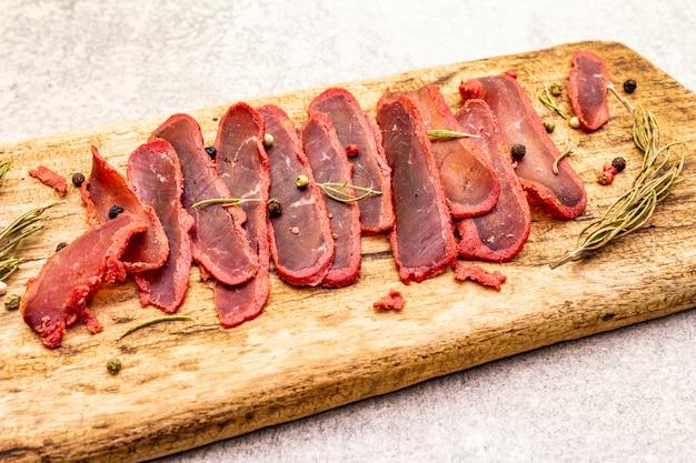Filet de viande de boeuf séchée avec du romarin sec et du mélange de poivre sur planche de bois vintage