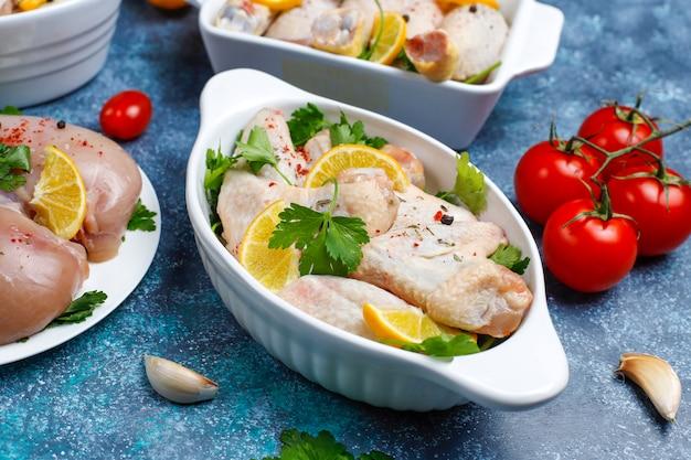 Filet de viande de poulet cru, cuisse, ailes et pattes aux herbes, épices, citron et ail sur fond bleu foncé. vue de dessus