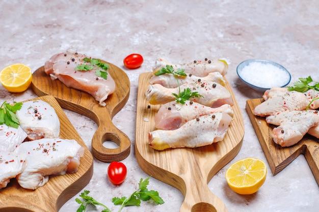 Filet de viande de poulet cru, cuisse, ailes et pattes aux herbes, épices, citron et ail. vue de dessus