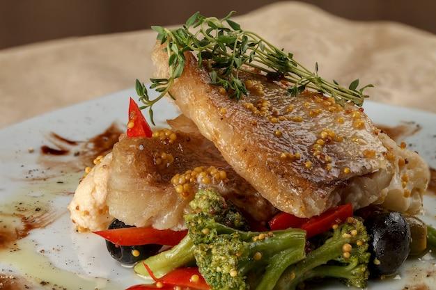 Filets de poisson blanc frits sur des légumes.