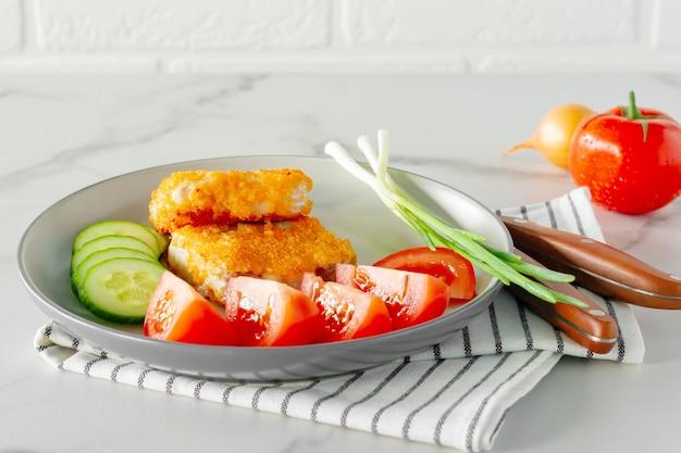 Filets de poisson panés frits avec tomates fourmis concombres servis sur une assiette en gros plan.