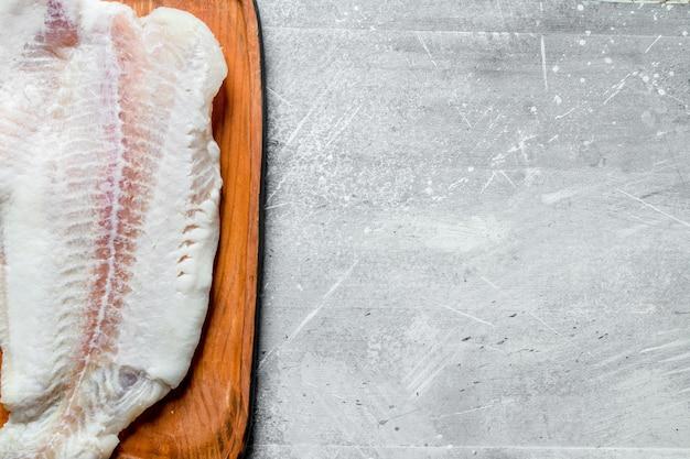 Filets de poisson sur la planche. sur fond rustique blanc