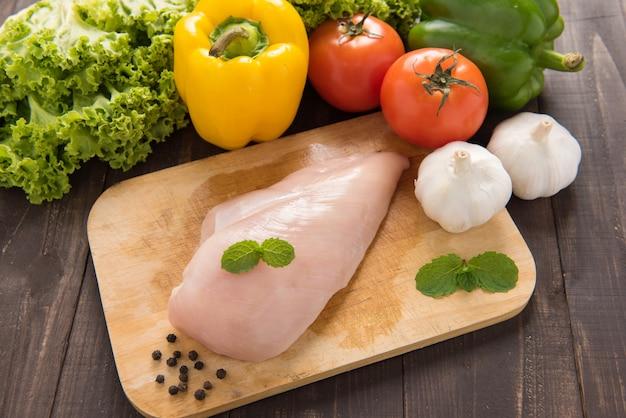 Filets de poitrine de poulet crus et légumes sur une table en bois.
