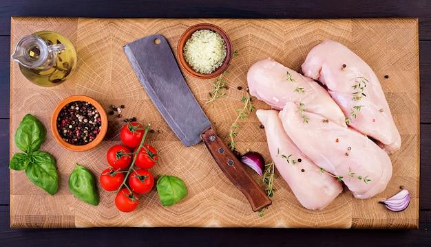 Filets de poitrine de poulet crus sur une planche à découper en bois avec des herbes et des épices. vue de dessus