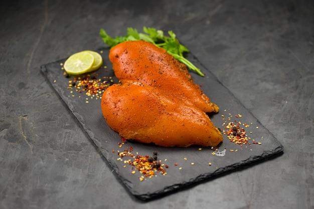 Filets de poitrine de poulet marinés disposés sur une planche de graphite