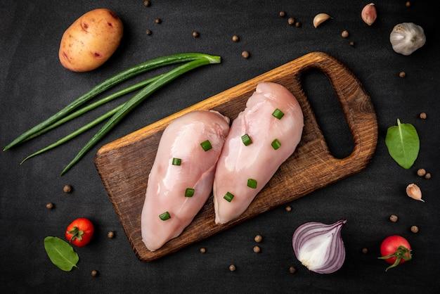Filets de poulet cru à l'oignon vert sur fond noir.