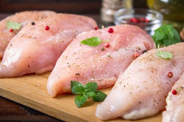 Filets de poulet cru sur une planche à découper dans le contexte d'une table en bois.