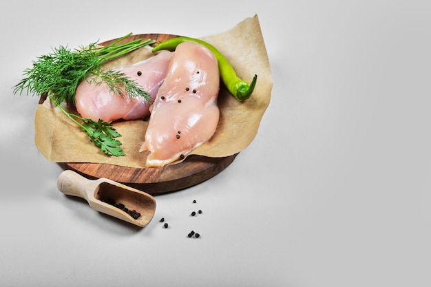 Filets de poulet cru sur plaque en bois avec cuillère