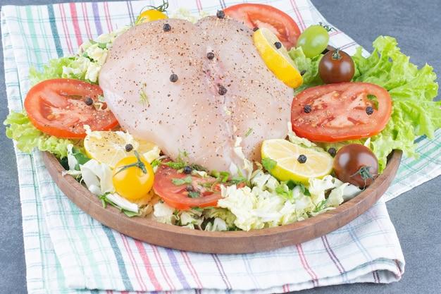 Filets de poulet et légumes tranchés sur plaque en bois.