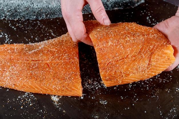 Les filets de saumon coupés à la main sur un tableau noir.