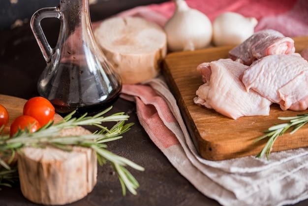 Filets de suprêmes de poitrine de poulet crus avec du piment, des grains de poivre et du thym. aux asperges et tomates pour accompagnement