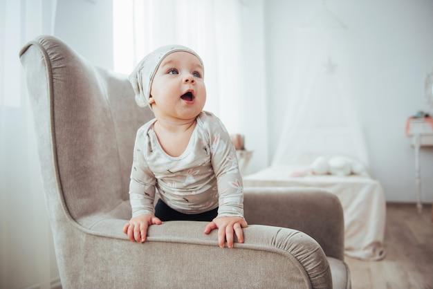 Fille de 1 an portant des vêtements élégants, assise sur une chaise vintage dans la chambre.