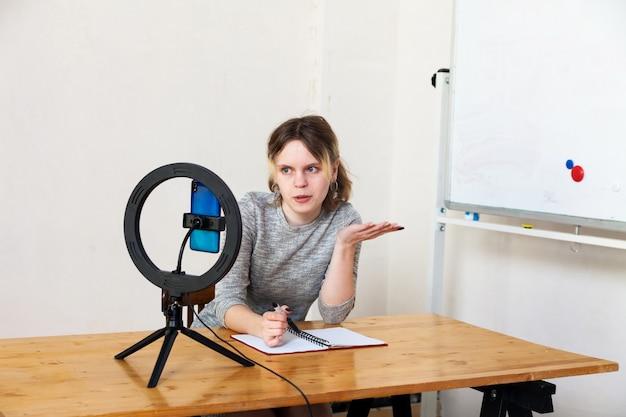 Fille de 16 ans d'enregistrement vidéo sur smartphone et s'éclairant avec une lampe annulaire à table dans une pièce lumineuse