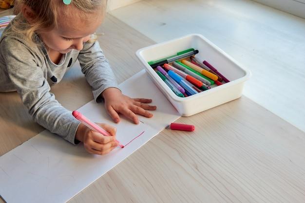 La fille de 3 ans dessine une image. enfant à la maison, jardin d'enfants et école maternelle fermés pendant covid-19