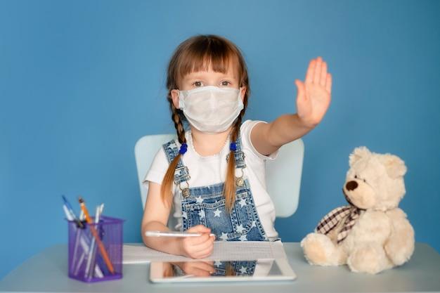 Une fille de 5 à 6 ans assise à une table effectue des tâches à distance sur la tablette. isoler sur un mur bleu. coronavirus, enfant masqué.