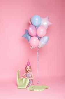 Fille de 5 ans le jour de son anniversaire dans une casquette avec ballons et ballons festifs