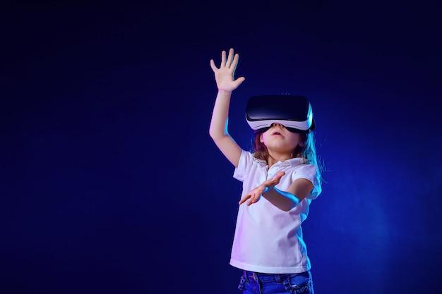 Fille 7 ans expérimentant le jeu de casque vr sur coloré. enfant utilisant un gadget de jeu pour la réalité virtuelle.