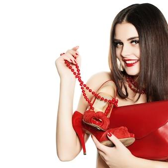 Fille accro du shopping avec des chaussures et des sacs à main de bijoux rouges isolés