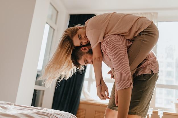 Fille accrochée au dos de son petit ami bien-aimé et sourit. les jeunes mariés sont méchants et passent du bon temps dans leur chambre lumineuse et confortable.