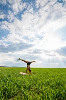 Fille acrobate effectue un appui renversé. le modèle se tient sur ses mains, faisant des écartements de gymnastique sur fond de piège vert et de ciel bleu, faisant du sport dans la nature
