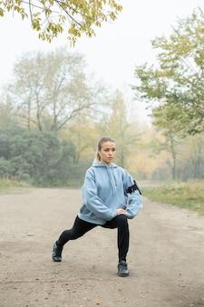 Fille active dans les écouteurs, sweat à capuche bleu, leggins noirs et baskets faisant de l'exercice pour étirer les jambes sur le chemin forestier contre les arbres le matin