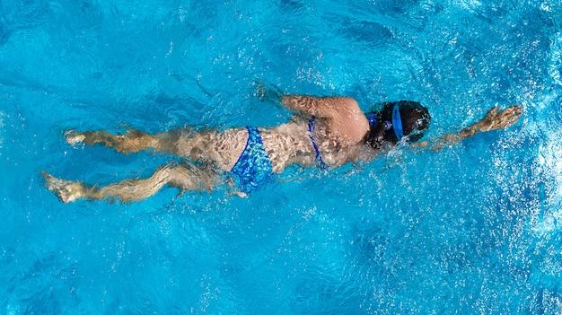 Fille active dans la piscine vue aérienne de drone d'en haut, jeune femme nage dans l'eau bleue, vacances tropicales, vacances sur concept resort