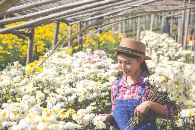 La fille admire les fleurs dans le jardin.