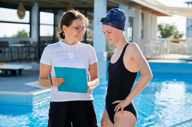 Fille adolescent nageur en maillot de bain sport avec entraîneur femme près de la piscine extérieure