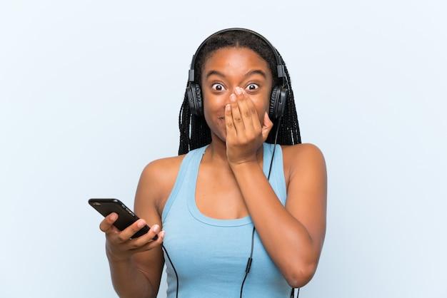 Fille adolescente afro-américaine avec de longs cheveux tressés écoute de la musique avec un téléphone portable avec une expression faciale surprise