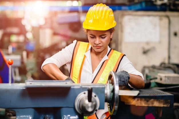 Fille adolescente afro-américaine travaillant dans l'industrie avec une lourde machine en acier.