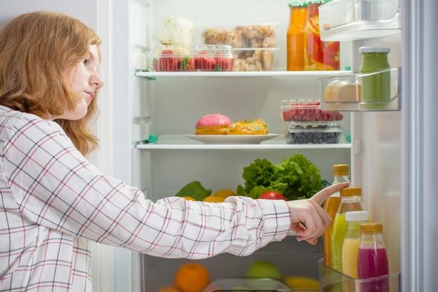 Fille adolescente au réfrigérateur avec de la nourriture