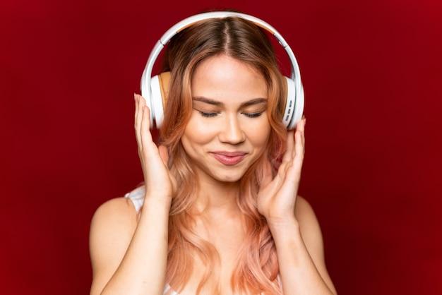 Fille adolescente aux cheveux roses sur fond rouge isolé à l'écoute de la musique