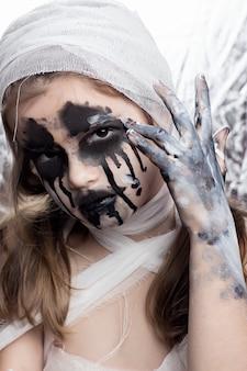 Fille adolescente avec des bandages de maman à halloween